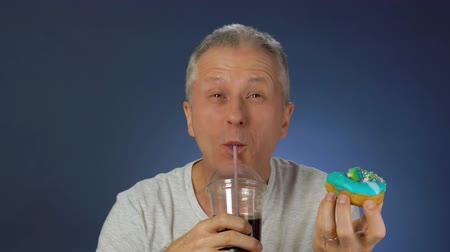hloupý : Funny middle-aged man funny eating cake, washing down his carbonated drink from a large glass with a straw.