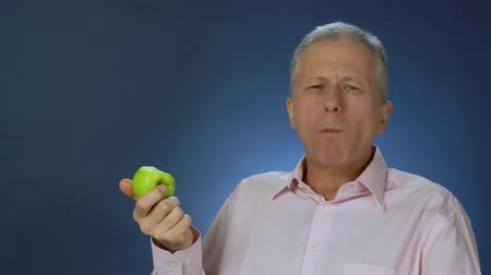 A slender middle-aged man in a pink shirt is happily eating a green juicy apple. Stock Footage