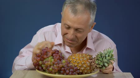 exotic dishes : A middle-aged man in a shirt happily eats grapes that lie on a large platter next to a pineapple, smiles and gives a thumbs up in approval.