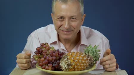 exotic dishes : A middle-aged man in a shirt slowly enjoying eating grapes lying on a large platter with pineapple and smiling.