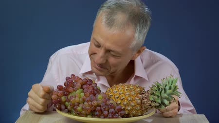 guloseimas : A middle-aged man in a shirt happily sniffs pineapple and slowly eats grapes, which lies on a large plate.