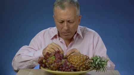 exotic dishes : A middle-aged man in a shirt quickly and happily eats grapes, which lies on a large plate next to a large pineapple. Stock Footage