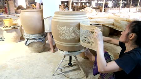 ratchaburi : Feb 18, 2017 - Ratchaburi, Thailand: female worker prints Dragon pattern on clayed jar, one of making famous Dragon Jar of Ratchaburi pottery industry.