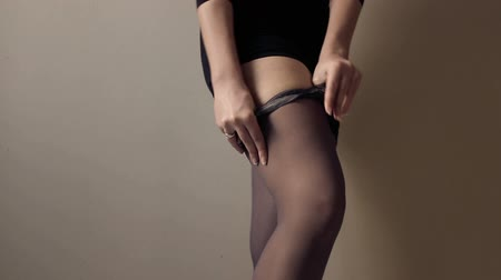 punčocháče : Young woman slowly taking off black stockings. Incognito. Concept of teasing and foot, nylon fetish, body beauty.