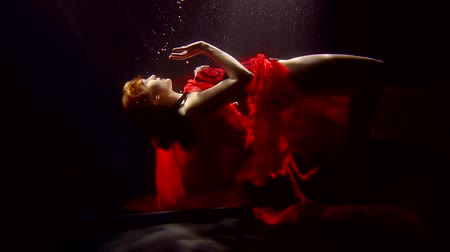 mar vermelho : Fascinating woman with pale skin dressed in a luxurious red dress floating up from the darkness. Vídeos
