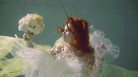 enchanted princess : young woman with long red hair underwater like in a fairy tale swims with a bouquet of flowers in her hand dressed in a decorated dress Stock Footage