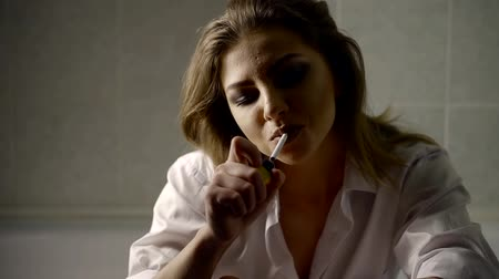 çakmak : Close up portrait of a sad woman in a bathroom using lighter for a cigarette. Stok Video