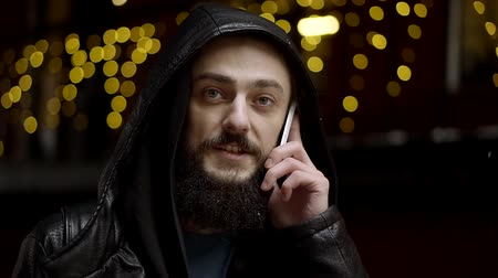 telefon : portrait of a bearded man with the phone, it says out on the street. snow falls and the lights of festive animation burn against the background