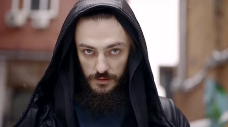 czarodziej : Close-up portrait of mysterious man with a beard in a leather cloak with a hood he is going day and smokes a cigarette