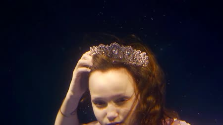 enchanted princess : confused and frightened little girl is looking around under water, she is taking off a crown Stock Footage