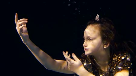 enchanted princess : little girl in a dark water of pool is drawning to the light her face and hands, crown of princess is on her head