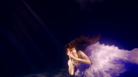 enchanted princess : dreaming girlie is falling on bottom of huge aquarium, smiling and playing with her loose hair, posing Stock Footage