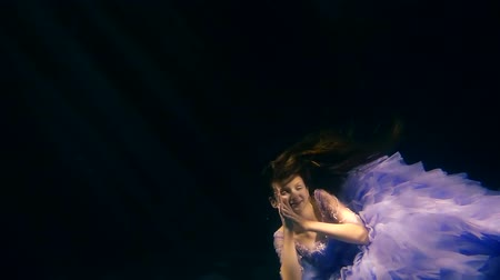 enchanted princess : brown-haired child girl is falling on an ocean bottom, smiling and touching her long hair