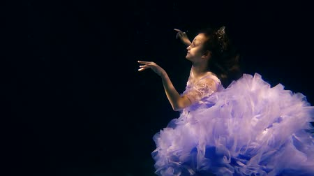 enchanted princess : preschooler girl is swimming in dark sea water at a depth and catching by her pretty face a beams of sun