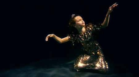 enchanted princess : little girl is sitting on a ground of ocean under water, wearing in golden shiny dress and crown, looking up Stock Footage