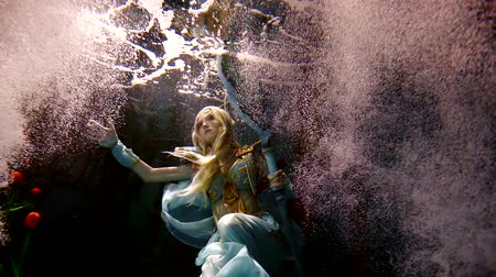 manó : Mysterious woman elf is standing underwater among dozens flowers and bubbles.
