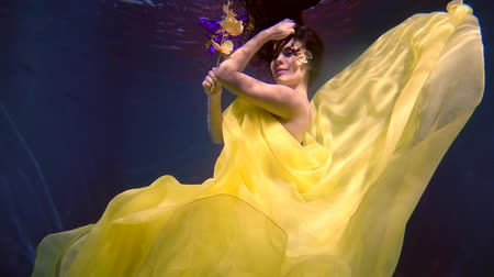 orquídeas : mysterious lovely slim woman dressed in yellow gown is floating underwater, holding orchid Stock Footage