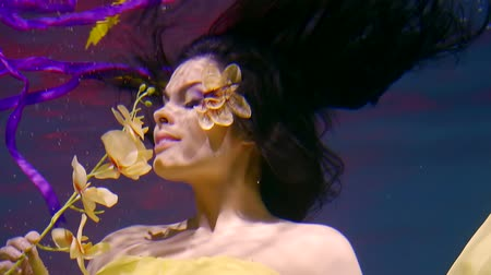 pétalas : romantic smiling girl is underwater, holding branch of yellow orchids, imaging smelling flowers Vídeos