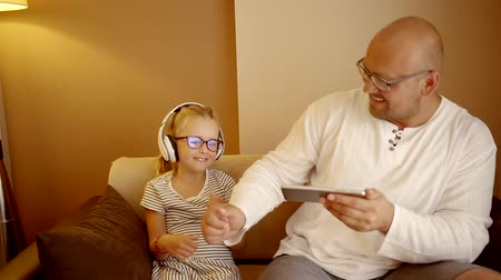 sluch : Nice family dad and daughter in glasses using technology, sitting on the couch at home. The man dances under music in wireless headphones Dostupné videozáznamy