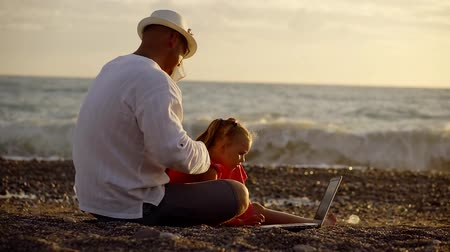 took : happy father rests with his daughter on the ocean. they took a laptop and connected to the wireless Internet. on the background of the waves and the sunset
