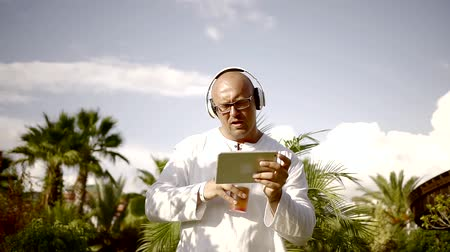 favori : bald drunk man dancing to the music with headphones and drinking alcoholic cocktail choosing a favorite track on a tablet device