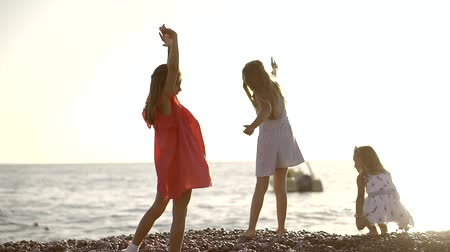 desobediente : three little girl is playing on a sea shore in summer time, they are throwing stones to a water