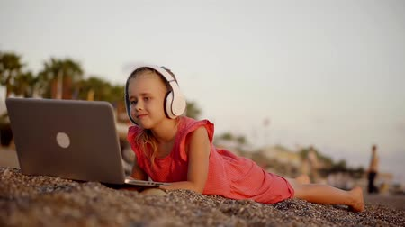 earpiece : calm little girl is watching video, using notebook and earpiece, lying on a shore of sea in sunset Stock Footage