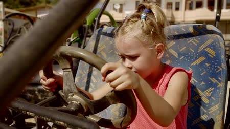quadbike : sad little girl is sitting behind the wheel of a old quad bike, can not turning the steering wheel