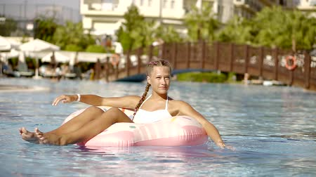 blue braid : cheerful teenage girl is floating on a pink rubber inflatable ring in a swimming pool in sunny day