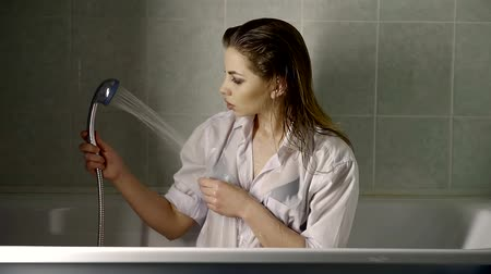 nedves : a young woman with makeup on her face holds a mixer in her hand from the bathtub and pours water on herself Stock mozgókép