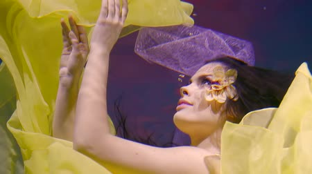 lem : a young actress dances a dance under the water, she is dressed in a bright yellow dress, and on her face there is a flower