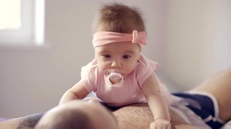 childrens : cute baby girl with baby pacifier is lying on belly and chest of her father in childrens room