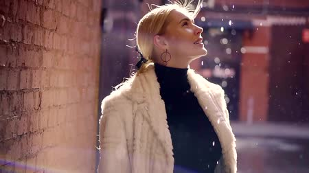 andar : a young and beautiful blonde is enjoying a spring day, the lady is smiling and watching as the rain drips from the roof, she is dressed in a warm and stylish coat