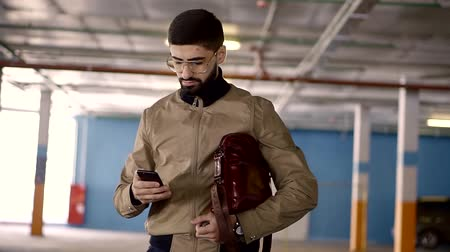гаджет : a young man with a thick beard holding in his hand an expensive smartphone and a branded bag, people who look like a businessman walking in a car park during the day