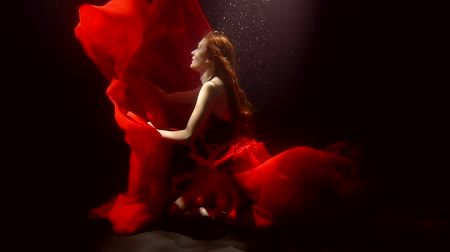 rudé moře : submerged woman with red hair and vivid red dress is in water in darkness, playing with fabric