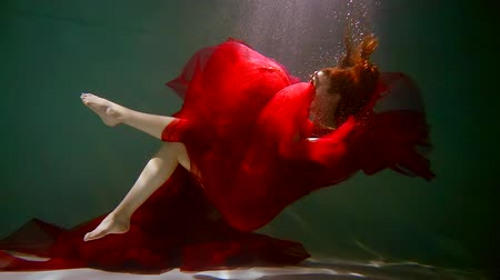 devanear : redhead girl id red long dress is falling in a pool and submerging to bottom, underwater slow mo Stock Footage