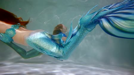 sereia : redhead playful mermaids are swimming in a water thickness of ocean, waving their colorful tails Stock Footage