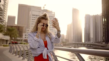 színezett : Stylish girl in round glasses tinted with white hair makes a photo of yourself on the cell phone. Tourist in UAE Dubai. Stock mozgókép