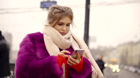 emissão : a young woman in a winter and a warm coat holds a smartphone and prints a message for her friends