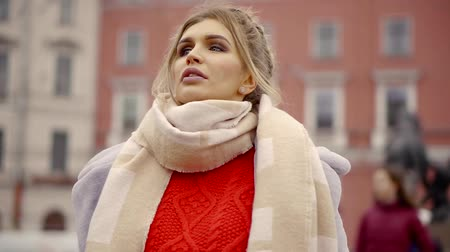 emissão : a young woman in a warm sweater and a winter coat strolling around the city, watching architecture Stock Footage