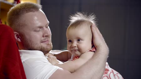 baby chubby : A young man holds his small and funny daughter in his arms, the child looks funny and funny