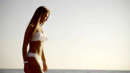 külot : A young woman in a sexy bathing suit goes along the beach and the sea, a lady with a good figure spends a vacation near the sea Stok Video