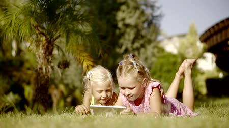 dětinský : Two funny girls lie on the grass in a warm sunny day, the sisters are holding a tablet in order to watch cartoons