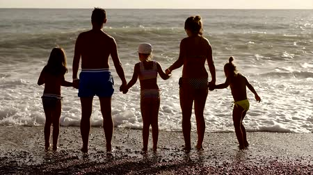 papucs : A friendly family stands near the waves on the beach, they hold hands and resist the waves during the holidays