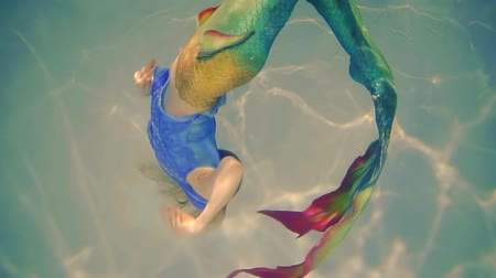 mermaid : girl in a mermaid costume performs a circular rotation in thickness of water