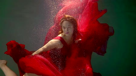 elves : girl in the red dress and the pattern on the face swims in the pool Stock Footage