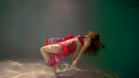 mermaid : slender girl in a bright dress floats in the weightlessness of water