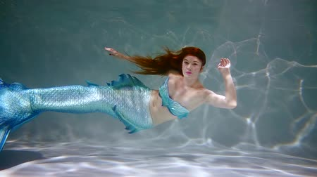 mermaid : young mermaid girl with long blue fish tail swimming under water. slow motion 500 fps
