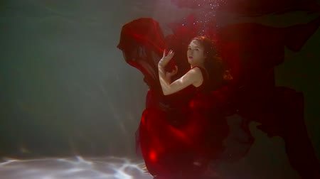 mermaid : noble graceful young girl in long red dress under the water . slow motion 500 fps