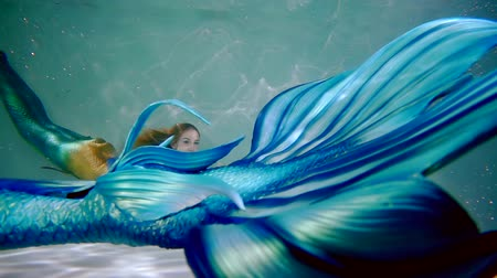 gracefully : elegant two girls mermaids gracefully swimming in the indoor pool Stock Footage